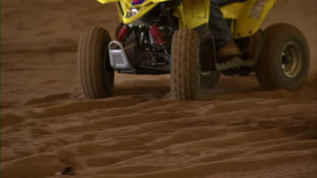 close up of the atv wheels as the vehicle drives around. - helm stock-videos und b-roll-filmmaterial