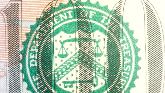 Close up of the Department of the Treasury symbol on the $100 bill