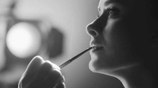 näring av skådespelerskans ansikte. make-up artist applicerar läppstift på läpparna med en sminkborste på set. svartvit video. - skådespelerska bildbanksvideor och videomaterial från bakom kulisserna