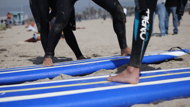 Close up of the feet of a tourist from Germany standing on a board and getting her first surf lessons on the beach of Venice Beach in Los Angeles...