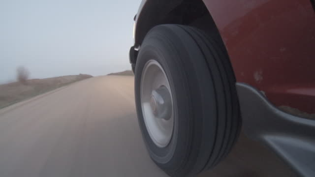 Close up of the front tire wheel of a late model SUV speeding down a barren dusty country gravel road with headlights glowing in the evening light as it crosses a bridge.
