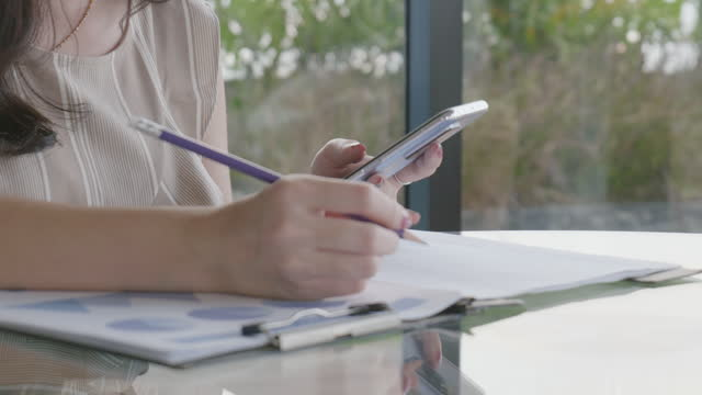 close up of the hand of a woman taking notes of the information obtained by searching online on a mobile phone - file clerk stock videos & royalty-free footage