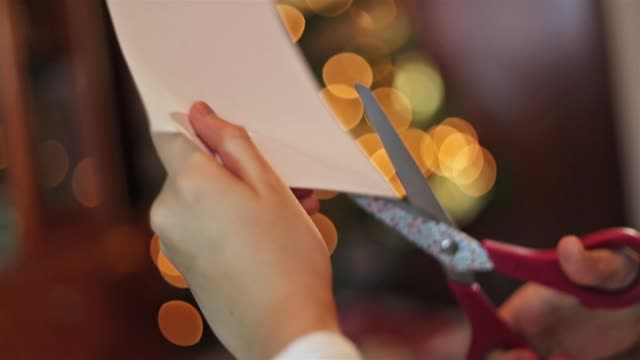 close up of the hands of a girl cutting a piece of paper with the christmas tree behind. - parte de una serie video stock e b–roll