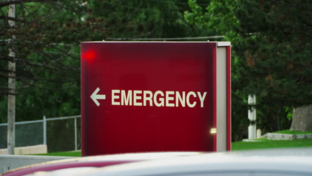 "vidéos et rushes de close up of the rear of an emergency ambulance as it drives past a generic hospital ""emergency"" sign. - panneau d'entrée"