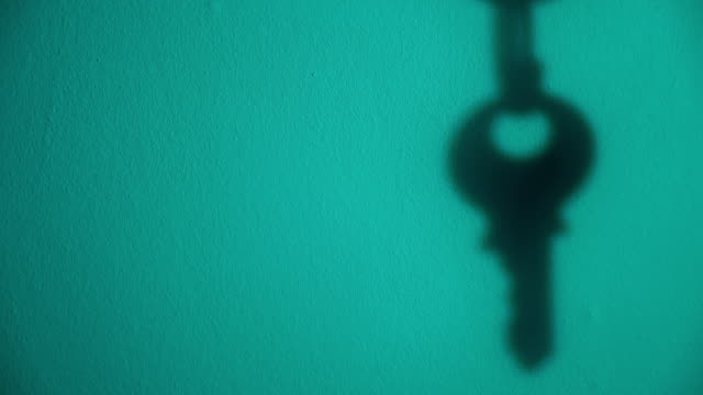 close up of the silhouette of a key which is hanging from a padlock. - hanging up stock videos & royalty-free footage