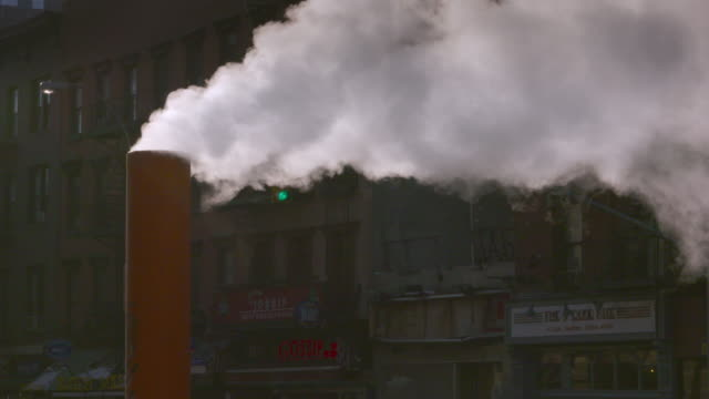 close up of thick steam emits from orange stack against city buildings as a background. - sfiatatoio video stock e b–roll