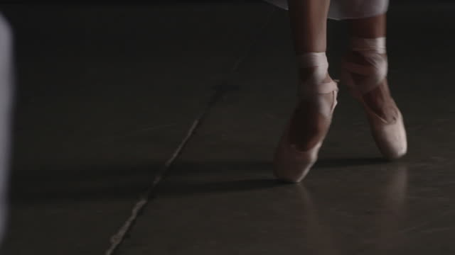 Close up of three ballerina's point shoes performing deboulé