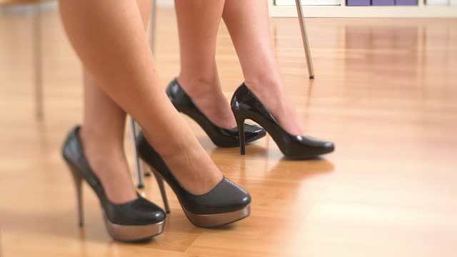 Close up of three business women's feet in high heels standing up and walking away