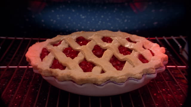 Close up of time lapse cherry pie baking and bubbling in oven
