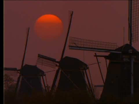 close up of time lapse sunset behind 3 windmills / holland - romantische stimmung stock-videos und b-roll-filmmaterial