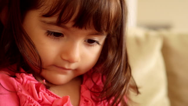 Close Up of Toddler's Face Looking Down Intently At Book