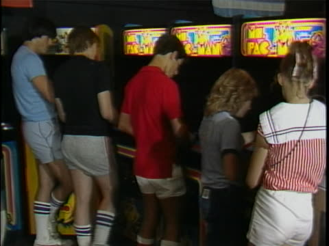 vídeos de stock, filmes e b-roll de close up of top of an arcade machine that has sign for ms. pac-man with logo. cut to wide shot of arcade hall that shows about 8 people standing... - cut video transition