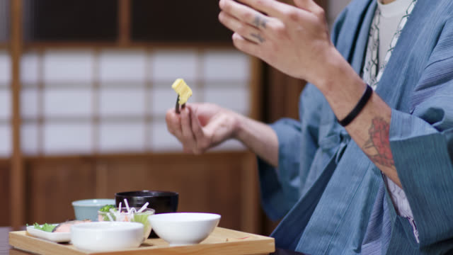 Close up of tourists in a Ryokan eating a traditional Japanese lunch