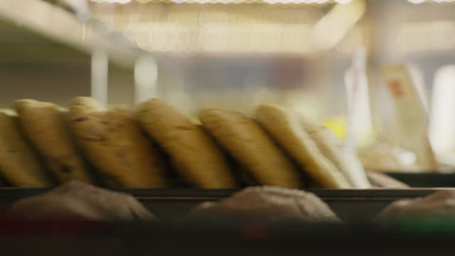 close up of tray of cookies sliding into bakery display case / salt lake city, utah, united states - präsentation hinter glas stock-videos und b-roll-filmmaterial