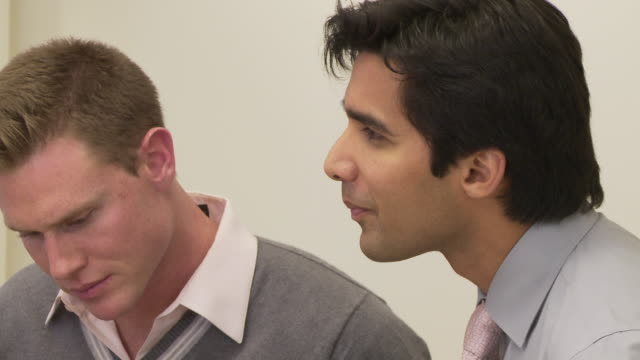 close up of two coworkers talking to group off screen - employee engagement stock videos & royalty-free footage