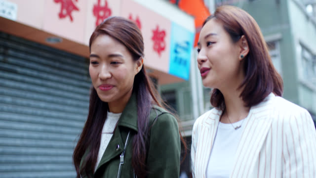 close up of two friends walking through the city - chinese ethnicity stock videos & royalty-free footage