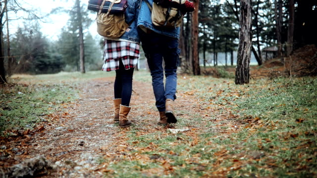 Close up of two hikers walking embraced in forest
