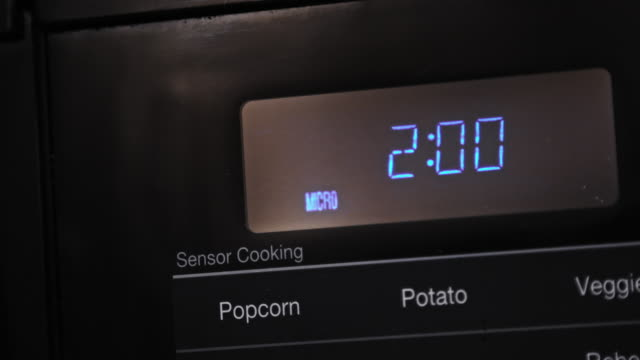 close up of two minutes entered and counting down cooking time on a black digital display microwave - microwave stock videos & royalty-free footage