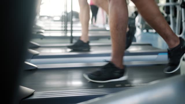 close up of two people running on treadmill - exercise machine stock videos & royalty-free footage