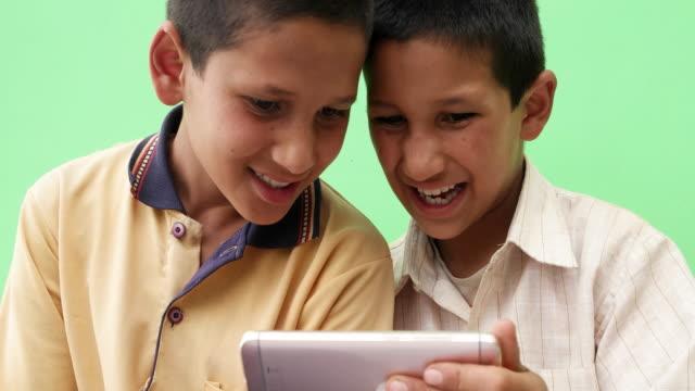 vídeos y material grabado en eventos de stock de close up of two siblings sharing a smart mobile phone device and getting entertained - camisa de polo