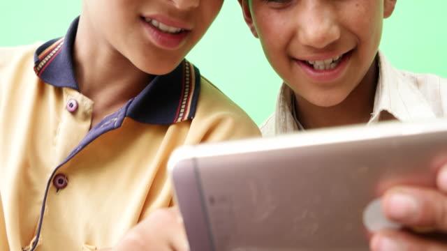 vídeos y material grabado en eventos de stock de close up of two siblings sharing a smart mobile phone device and getting entertained - nativo digital