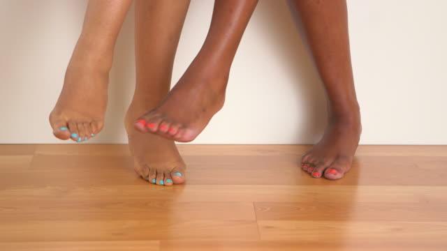 close up of two women's bare feet dancing - 胡坐点の映像素材/bロール