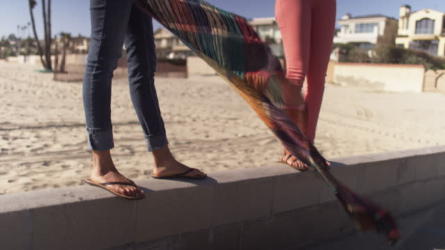 close up of two womens feet standing on wall at beach - sandal stock videos and b-roll footage