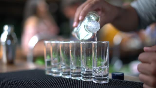 Close up of unrecognizable bartender serving shots of liquor