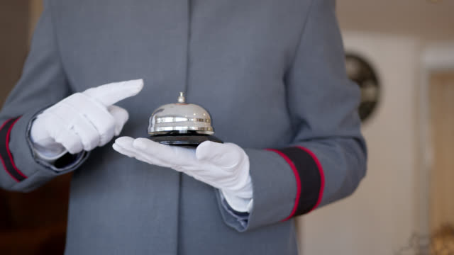 close up of unrecognizable bellhop ringing a bell at hotel - service occupation stock videos & royalty-free footage