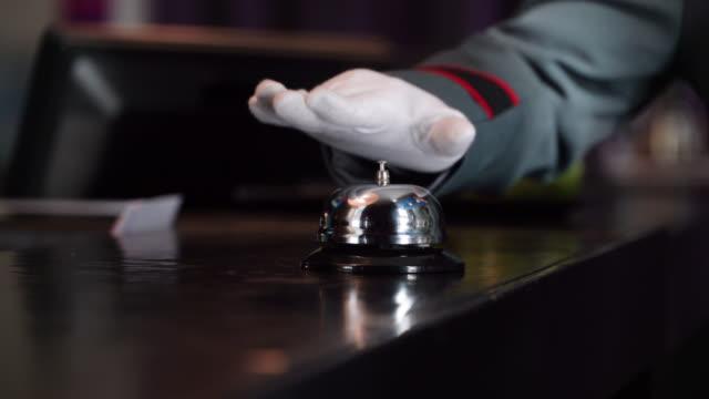 stockvideo's en b-roll-footage met close-up van onherkenbaar bellhop rinkelen een bel op hotel check-in teller - dienstverlener