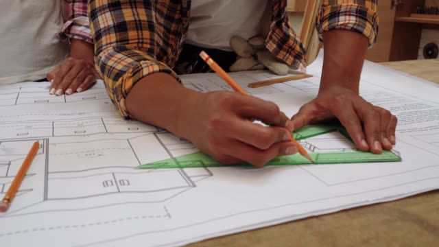 close up of unrecognizable carpenter couple working on a blueprint of a furniture design - blueprint stock videos & royalty-free footage