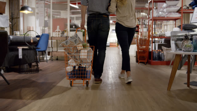 close up of unrecognizable couple shopping at a furniture store and pulling a cart with products - decor stock videos & royalty-free footage