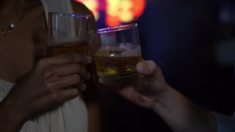 close up of unrecognizable couple toasting with whiskey at a bar - honour stock videos & royalty-free footage