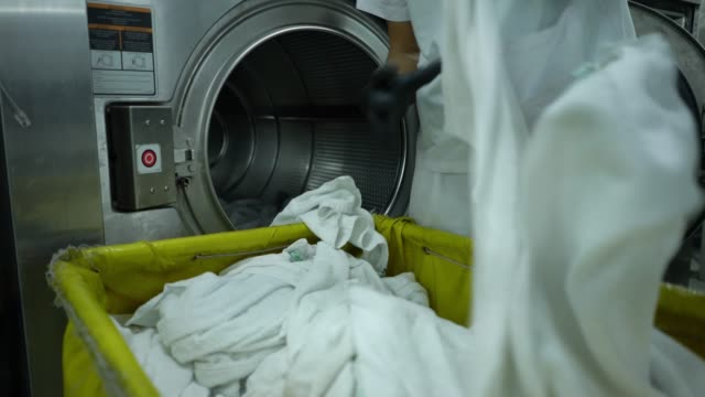 close up of unrecognizable employee loading washing machine with white towels - launderette stock videos & royalty-free footage