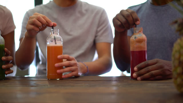 Close up of unrecognizable group of friends sitting at the counter and enjoying juices at a juice bar