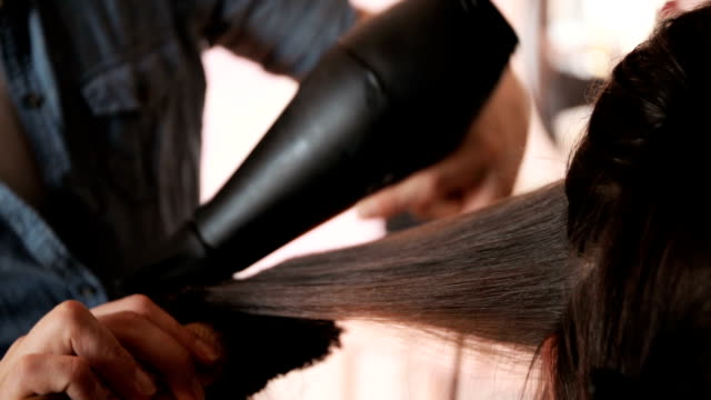vídeos de stock e filmes b-roll de close up of unrecognizable hairdresser using hair dryer and round brush while drying customers hair. - cabelo comprido