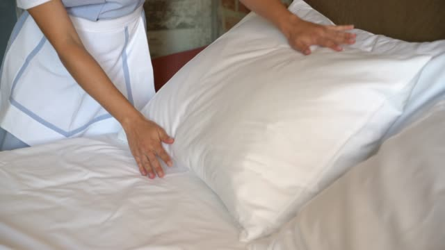 Close up of unrecognizable house keeper putting the pillows on bed