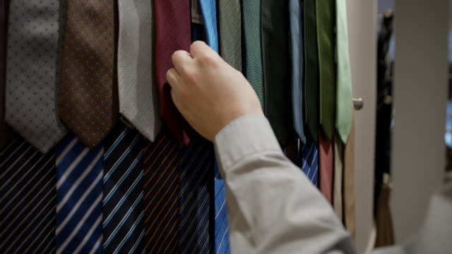 vidéos et rushes de fermez-vous vers le haut du client masculin méconnaissable choisissant une cravate de l'affichage à un magasin d'hommes - cravate