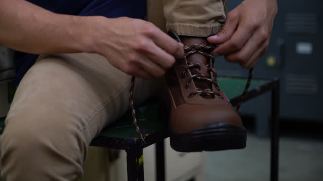 close up of unrecognizable man putting on his working boots and trying them - stivale video stock e b–roll