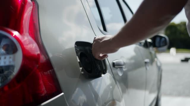 vídeos de stock, filmes e b-roll de feche acima de homem irreconhecível trabalhando em um posto de gasolina reabastecendo um tanque de gasolina - motor