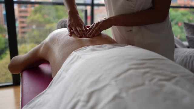 nahaufnahme der nicht wiederzuerkennenden masseurin massiert einen männlichen kunden zu hause - hausbesuch stock-videos und b-roll-filmmaterial