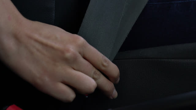 close up of unrecognizable person buckling the seat belt - belt stock videos & royalty-free footage