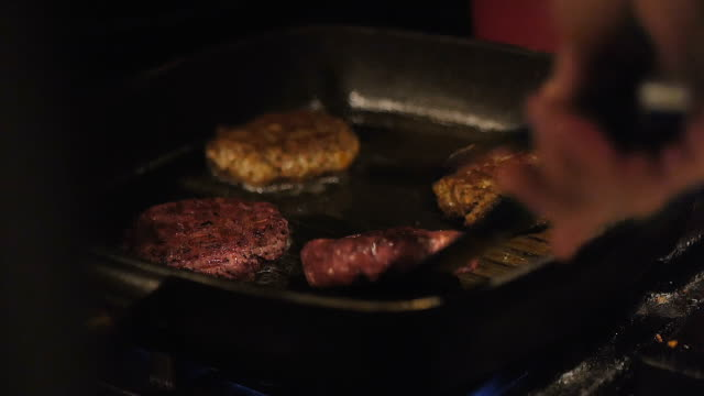close up of vegetarian burger grilling on a griddle pan. healthy food. - vegan food stock videos & royalty-free footage