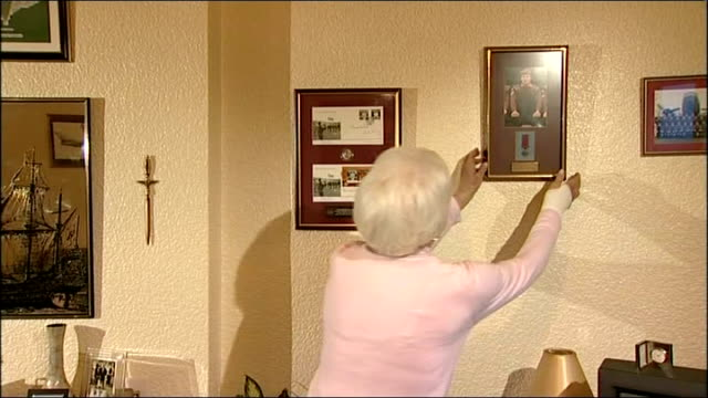 close up of victoria cross medal displayed in frame freda mckay as removes framed photograph of her son from wall sot freda mckay interview sot goes... - the victoria cross stock-videos und b-roll-filmmaterial