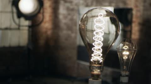close up of vintage industrial lightbulb, rack focus to vintage movie light - brick stock videos & royalty-free footage
