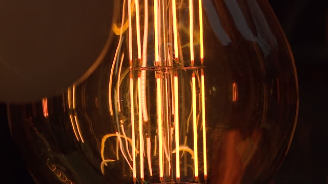 close up of vintage retro edison style light bulb with squirrel cage filament - filament stock videos & royalty-free footage