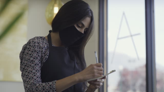 close up of waitress wearing protective face mask taking order in restaurant / orem, utah, united states - cafe stock videos & royalty-free footage
