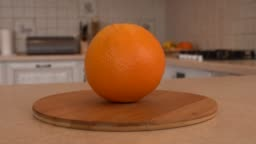Close up of whole orange fruit. Rotating camera with white kitchen on the background. Dolly-shot.