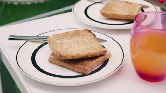 close up of whole wheat toast on a breakfast table in home outdoor garden. - chair stock videos & royalty-free footage