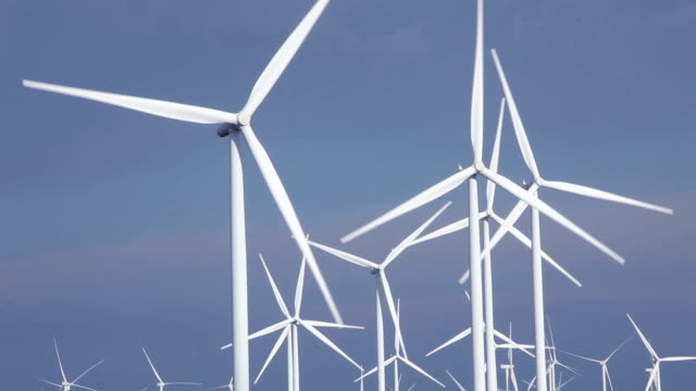 close up of wind turbines in blue sky - attrezzatura industriale video stock e b–roll